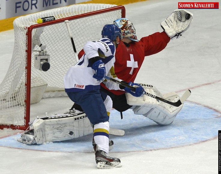 Switzerland's goalkeeper Reto Berra, right, saves the puck against Kazakhstan's Yevgeni Bugamin, left, during the Ice Hockey World Championships preliminary round group match between Switzerland and Kazakhstan at the Hartwall Arena in Helsinki