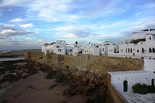Asilah, Morocco. The Wall of the Old Medina facing the Atlantic Ocean. La Medina di Asilah è piccola e molto compatta. Interamente racchiusa da mura occupa uno spazio lungo circa quattrocento metri e largo non più di duecento.  Il suo lato occidentale si affaccia su una scogliera ed una piccola spiaggia. Un scenografico bastione domina l'oceano, al tramonto è qui che convergono tutti i turisti.