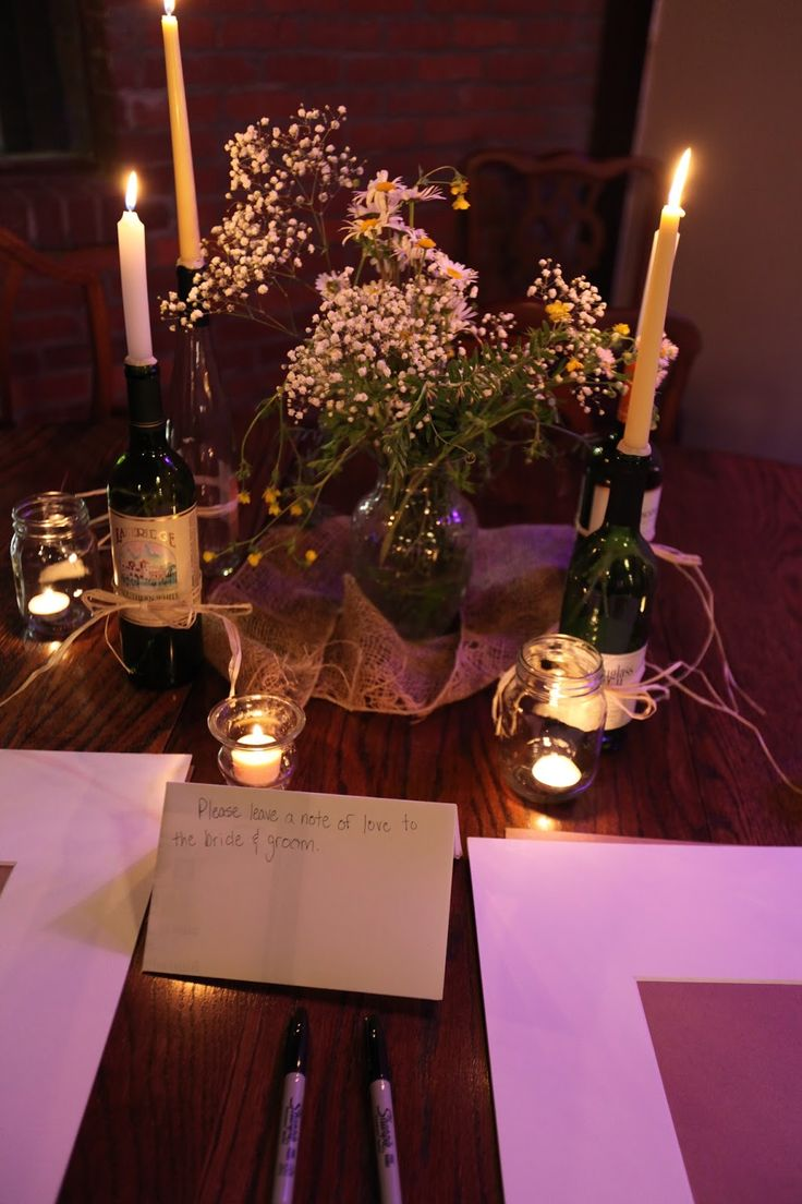 Baby's breath. wildflowers. burlap. candles in wine bottles at the sign in table for the