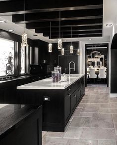 The exposed beams paired with crystal, sparkling pendant lights bring glamour to this contemporary kitchen.