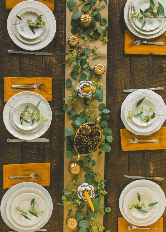 paper runner, foliage, berried stems, candles, gilded 'pumpkins'. See food and drink board or source post for image of same table with Thanksgiiving food.