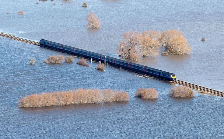 A First Great Western train makes its way across the flooded Somerset Levels Picture: JAMES DADZITIS/SWNS