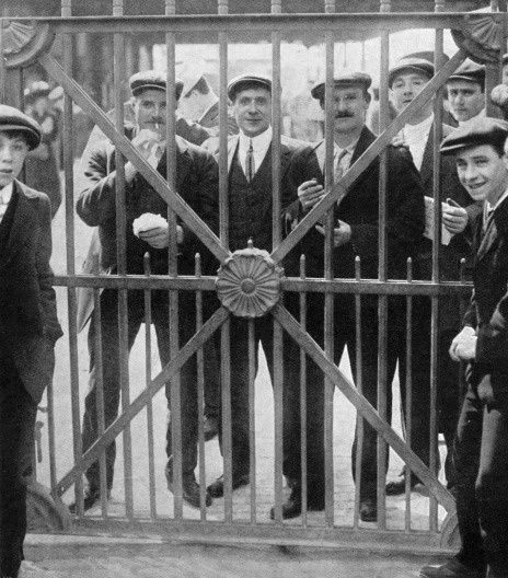 Crew members of Titanic who were detained as possible witnesses - there was a delay in sending the wire to tell them they could leave of their own volition. Here they are looking through closed dock gates at Plymouth on 4th May, 1912  B. Lowe