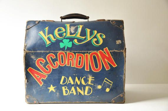 What a unique, beautiful find this is! This old accordion case, so beautifully aged and so full of character, must have travelled a lot and seen so many places and people! It has such rich colors, and wonderful graphics. On the front side it writes Kellys Accordion Dance Band that I assume must be an irish band. This wonderful piece of luggage will certainly add character to any space.  The case is worn and and has some tearing and scuffing, especially along the edges. The inside shows wear…