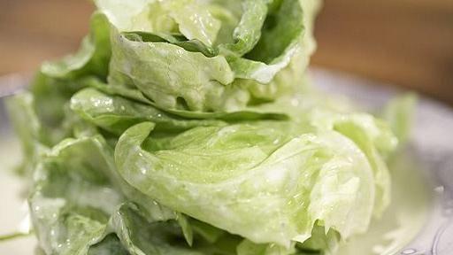 Vom Kopfsalat die äußeren Blätter entfernen. Den Kopfsalat im Ganzen in stehendem kalten Wasser waschen und abtropfen lassen, den Strunk herausschneiden und die Blätter trocken schleudern.Schmand, Zitronensaft, Zucker und Salz in einer...