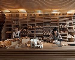 """""""melbourne-based architecture practice march studio has shared with us images of 'baker d. chirico',  an interior project for a new branch of the artisanal bakery in carlton, australia. seeking to stay simple  and true to the product, the design features an undulating CNC-routed plywood form that lends   a dynamic sense of space to the narrow shop in addition to providing shelving for the bread"""""""