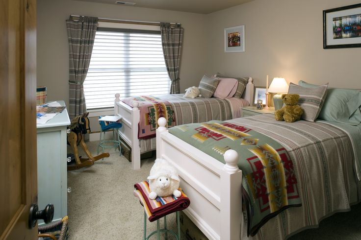 Traditional kid's room two twin beds, striped bedding, a southwestern design, neutral walls and plenty of toys. Seems like the perfect kid's room. #kidsroom #kidsbedroom