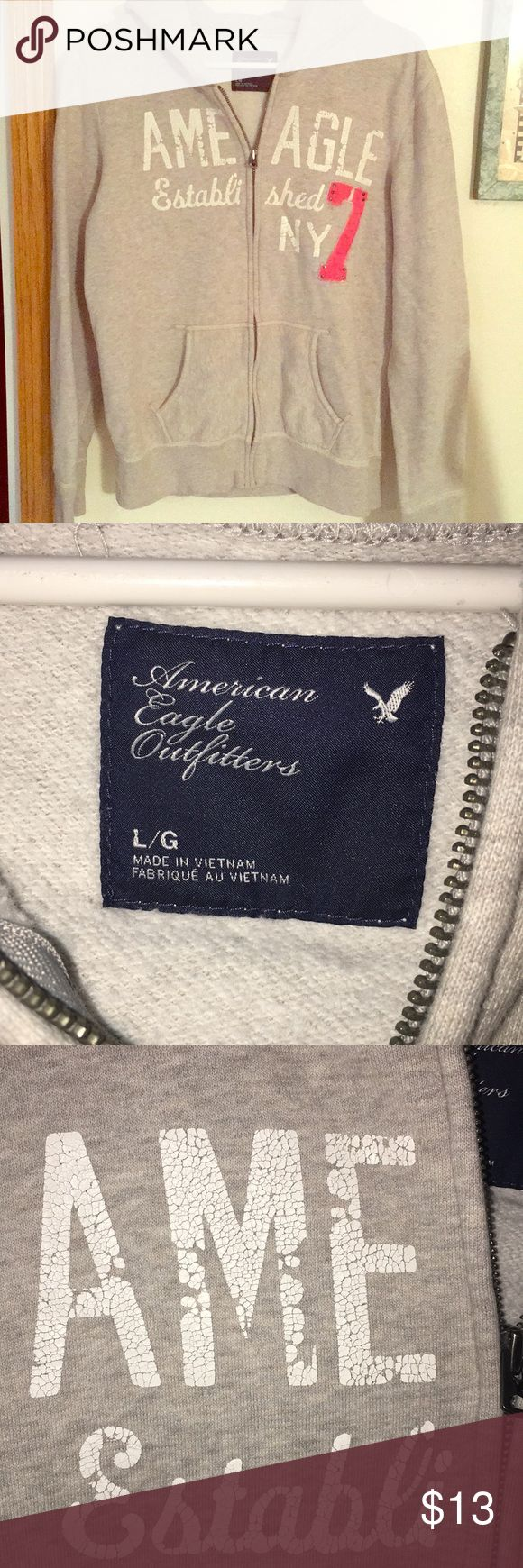 Lg Grey Womens American Eagle Zip Up Hoodie Large Women's American Eagle grey zip up hoodie with a pink 7. Used in great condition. American Eagle Outfitters Jackets & Coats