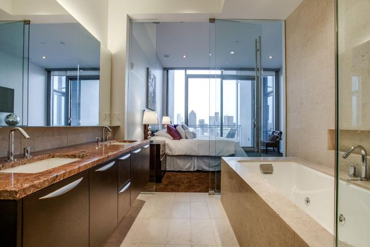 A spacious master bath connects to the two master bedrooms at this luxury penthouse. A soothing neutral palette and glass doors evoke a spa-like feel. Sleek fixtures, frameless mirrors and a floating double vanity complete the modern design.