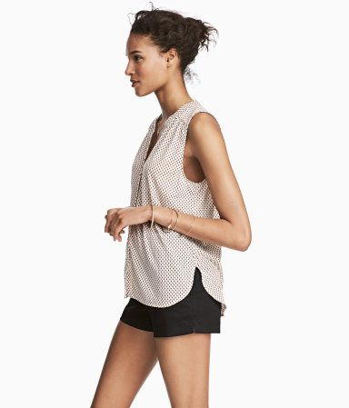 Light beige/patterned. Sleeveless top in soft viscose jersey with a printed pattern. V-neck, buttons at front, and yoke at top. Slits at sides.