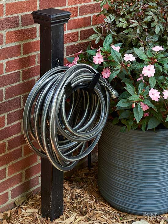 To corral a hose in style, set a 4x4 pressure-treated wood post a foot into the ground using fast-setting concrete. Top it with a post cap, paint the assembly glossy black, and install a wall-mounted metal hose rack.