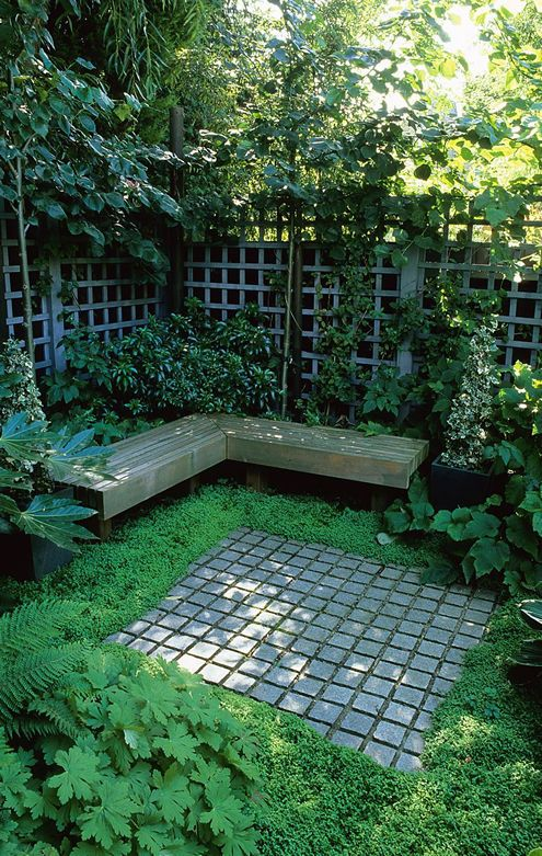 Shady seating luxuriantly planted in a composed town garden designed by Acres Wild.