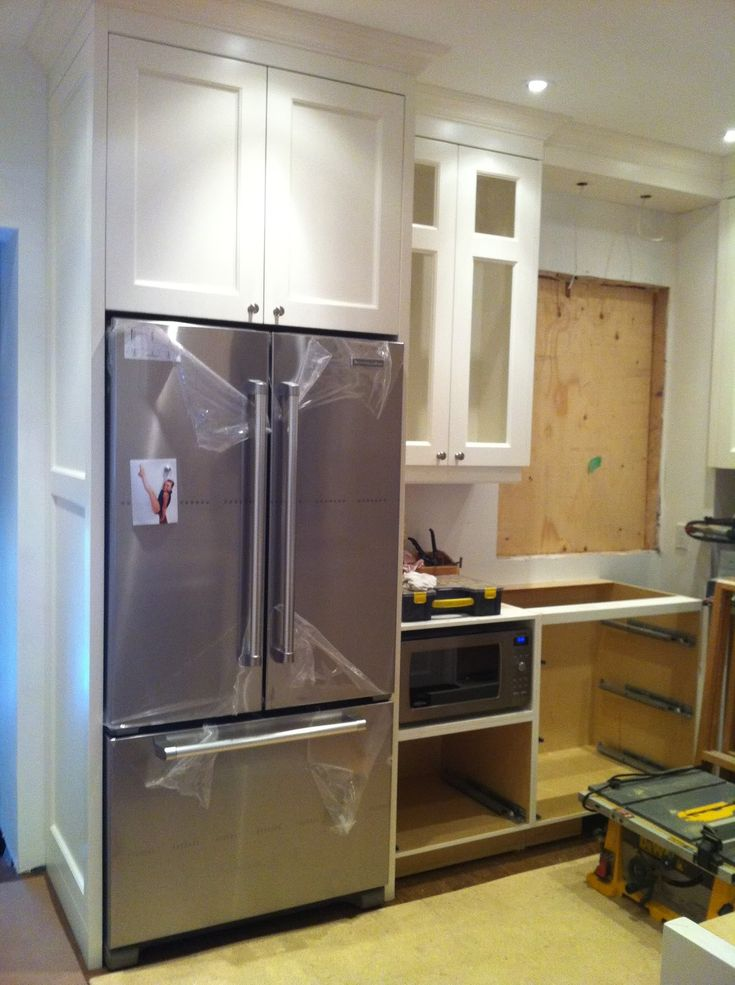 Encapsulate refrigerator and bring countertops forward for a custom, built-in look.