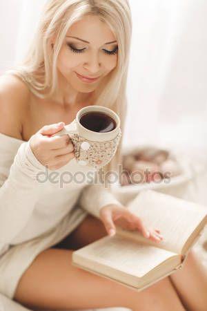 Scarica - Giovane bella donna - bionda, indossa una maglia calda breve vestito fatto a mano, leggero - beige, leggendo un libro con una tazza di caffè in mano, sdraiato sul divano a casa in camera da letto — Immagini Stock #62059179