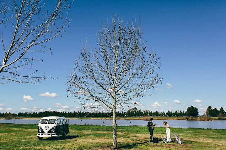 Peter D Photography shows the bride and groom with their Kombi van next to the lagoon at the Sydney Polo Club.