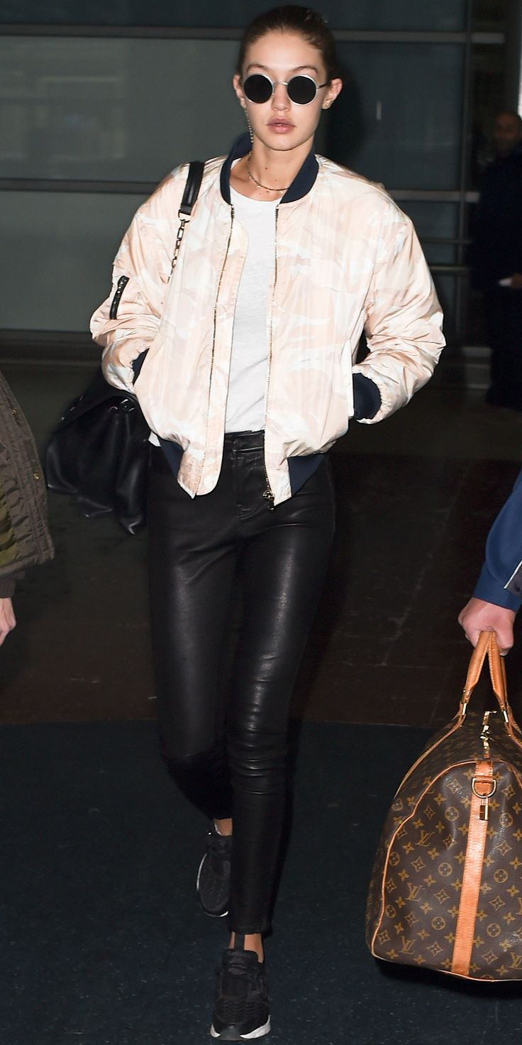 GIGI HADID The model was the epitome of jet-set cool in this silky light pink bomber and slim black leggings. Comfy black sneakers and round eye sunglasses finished off the no-fuss look.