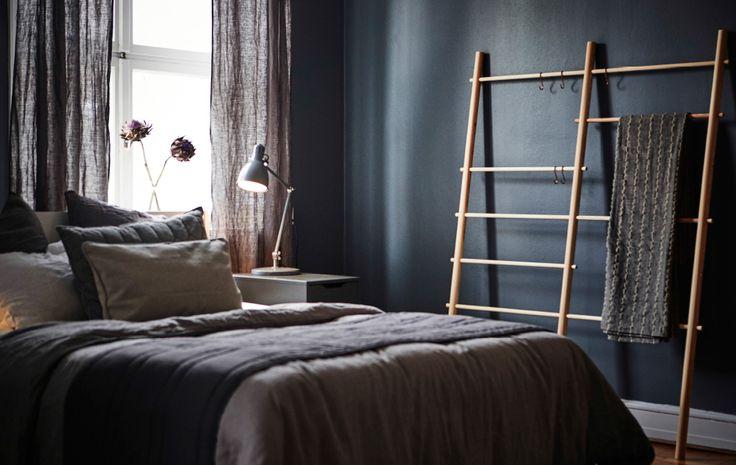 Soveværelse med mørke vægge med vindue, seng, sengebord og stige til plaider.