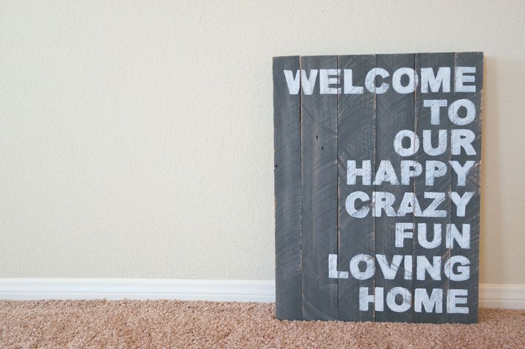 """Custom """"Wecome to our happy, crazy, fun, loving home"""" Wooden Pallet Sign by M.E. Refined Designs. Finished in a dark grey paint with white hand painted lettering."""