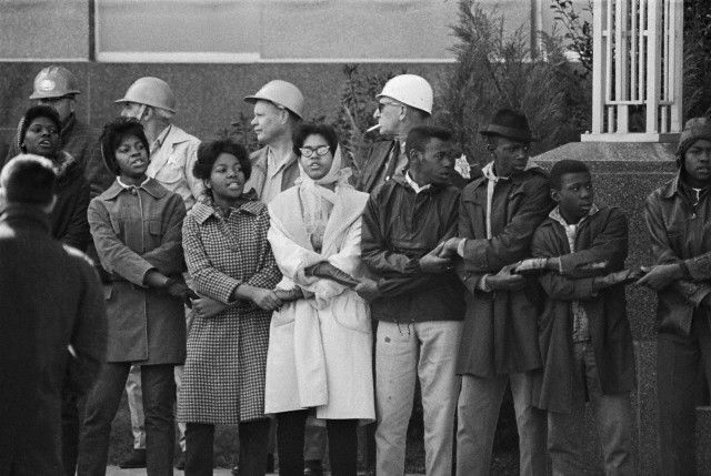 Civil rights demonstrators link hands and sing during a protest at the Dallas Country Courthouse ...