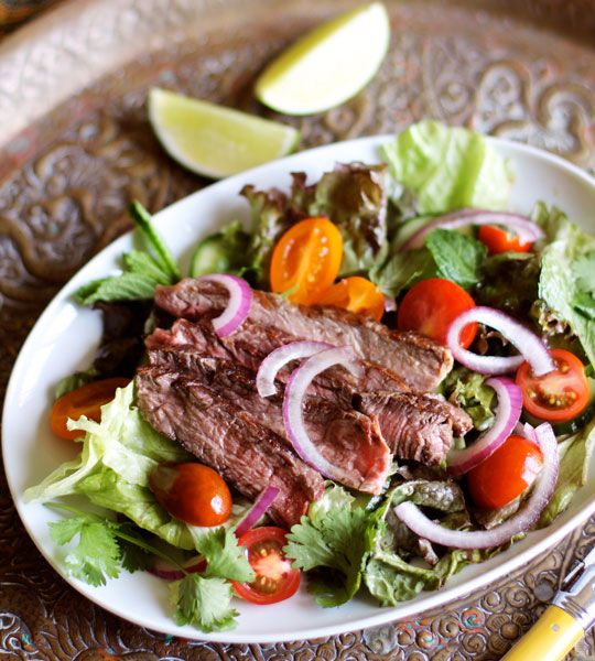 Thai grilled steak salad. 1 1/2 pounds rib eye steak. 1/4 cup lime juice; 1/4 cup fish sauce; 1/2 teaspoon sugar; 1 small head lettuce; 1/2 cup mint; leaves; 1/2 cup cilantro leaves  1 cucumber, thinly sliced; 1/2 pint cherry tomatoes, halved; 1/4 red onion, thinly sliced; Salt; Vegetable oil.
