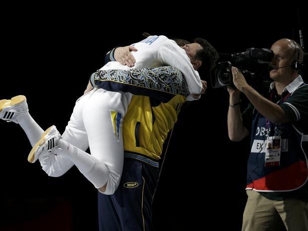 A ucrânia Yana Shemyakina comemora a sua vitória dando um abraço em seu treinador após derrotar a alemã Britta Heidemann durante a luta pela medalha de ouro dos Jogos Olímpicos  Foto: Reuters