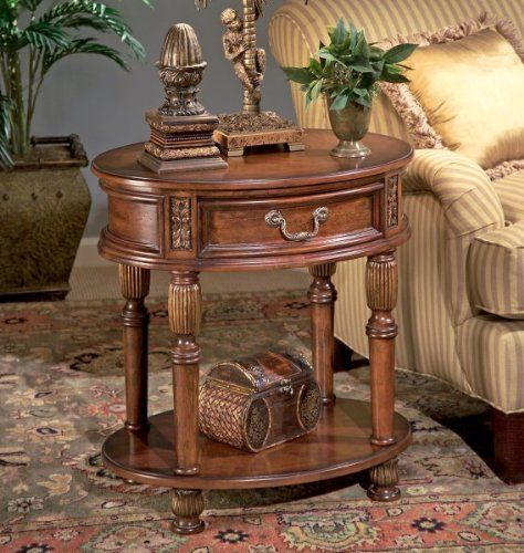 "Butler Specialty 1305030 Oval Accent End Table, Butler Hallmark by Butler Specialty Company. $349.00. Made from hardwood. Catch-all drawer. Color: Olive Ash Burl / Cherry / Antique Brass. Size: 26""H x 24""W x 18""D. Hand carved accents. Finish:Butler Hallmark  Oval Accent Table  Selected hardwoods and choice veneers.  Hand carved details.  Olive ash burl veneer top and lower shelf with cross-grain cherry veneer borders.  Antique brass finished hardware on drawer."