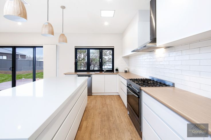 Streamlined handle free cabinets, white matt subway tiles and fresh timber bench and flooring