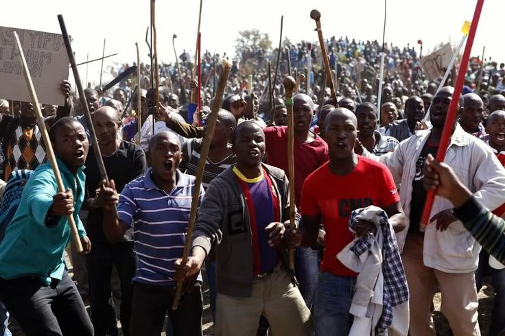 Marikana: A year on | Protesters sing as they hold weapons.