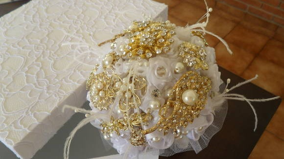 Buque com broches, flores de tecido, cristais, pérolas de vidro e plumas