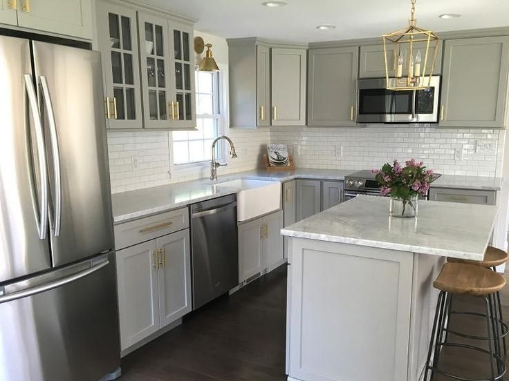 Gray kitchen features gray shaker cabinets adorned with brass pulls by Lewis Dolan paired with honed carrera marble countertops and a white mini subway tile backsplash.