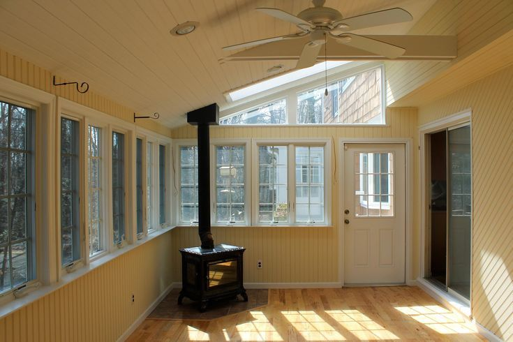 beautiful sunroom with a working wood burning stov…