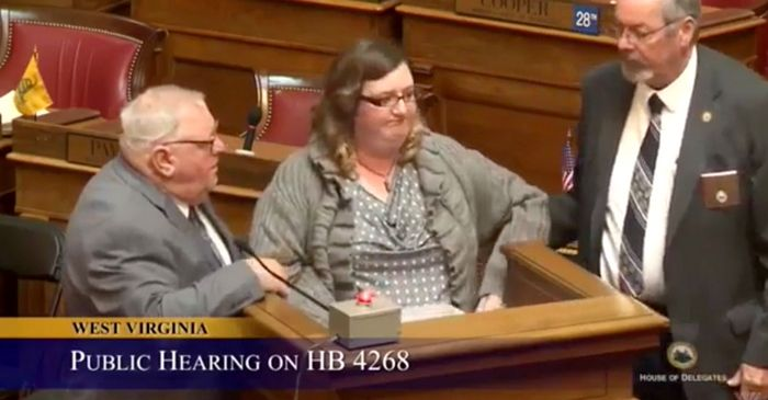 A woman was dragged away from a public hearing by security for listing the 'donations' made to the politicians in support of a bill by big oil.