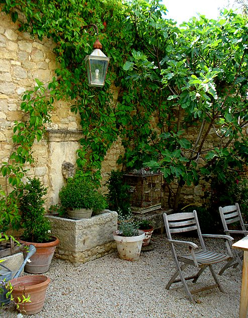 French garden with stone wall, fountain & gravel