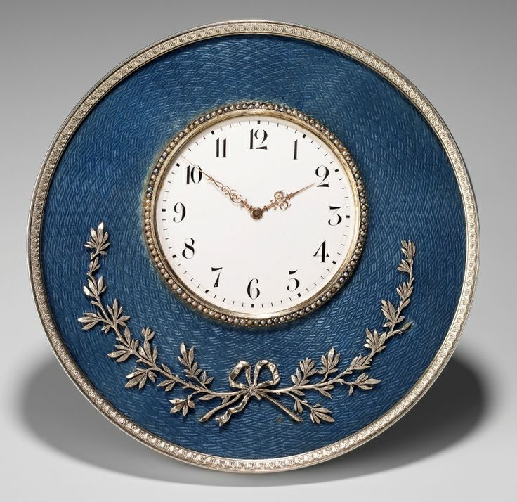 In March 1959 The Queen purchased this clock from Wartski for £430. The clock was made in the workshop of Henrik Wigström and is of Prussian blue guilloché enamel with silver mounts, and the bezel is set with seed pearls. The movement was supplied by H. Moser & Cie. Mark of Henrik Wigström; silver mark of 88 zolotniks (1896-1908); FABERGE in Cyrillic characters