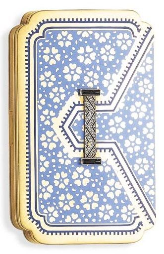 AN ART DECO ENAMEL, DIAMOND AND GOLD COMPACT, BY CARTIER. Of stylised envelope design, the blue enamel and gold floral motif lid enhanced by an applied rose-cut diamond and black onyx plaque, to the blue enamel striped sides, opening to reveal a fitted mirror, lipstick and powder compartment, mounted in 18K gold, circa 1925, with French assay marks and maker's mark. #Cartier #ArtDeco #compact