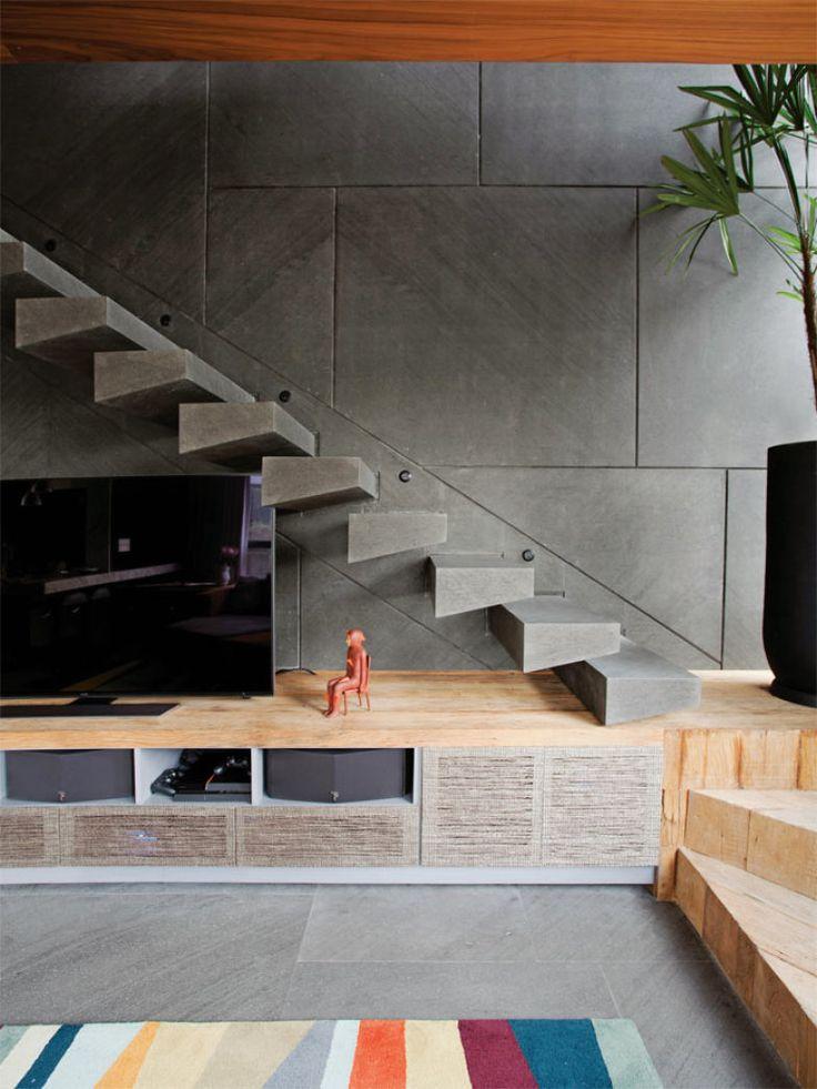 A parede e a escada foram revestidas de mármore basaltino (Mont Blanc). Na parte de baixo, a estrutura de madeira de demolição forma a bancada do móvel da TV e também um lance de degraus.
