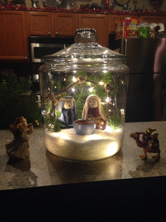 "My version of the cookie jar Snowglobe with nativity set my Mom made out of terra cotta pots. I made the crèche out of twigs and twine and added a string of lights on a wire that are battery operated which I partially stuck under the Epsom Salt ""Snow"". I added real greenery inside and out with an angel and magi ornament I had. Too cute."