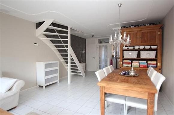 Ruime tuingerichte woonkamer met open trapopgang naar de for Wand woonkamer