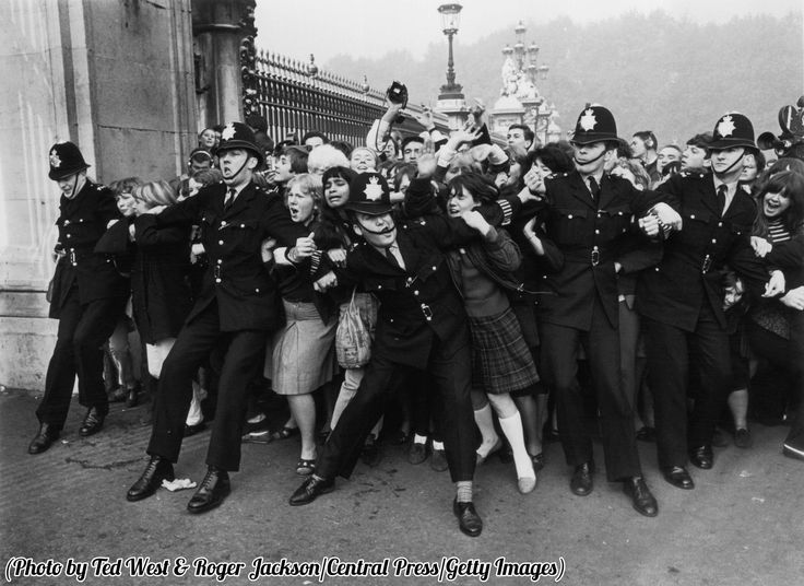 Police keeping back a crowd of young Beatles fans outside Buckingham Palace, London, 1965.