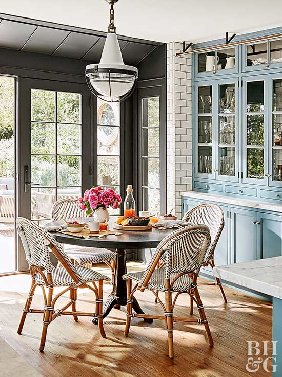 Julianne created an informal and intimate breakfast nook at one end of the kitchen with floor-to-ceiling breakfront cabinetry that works like a hutch, a pedestal table, and rattan bistro chairs with woven seats.