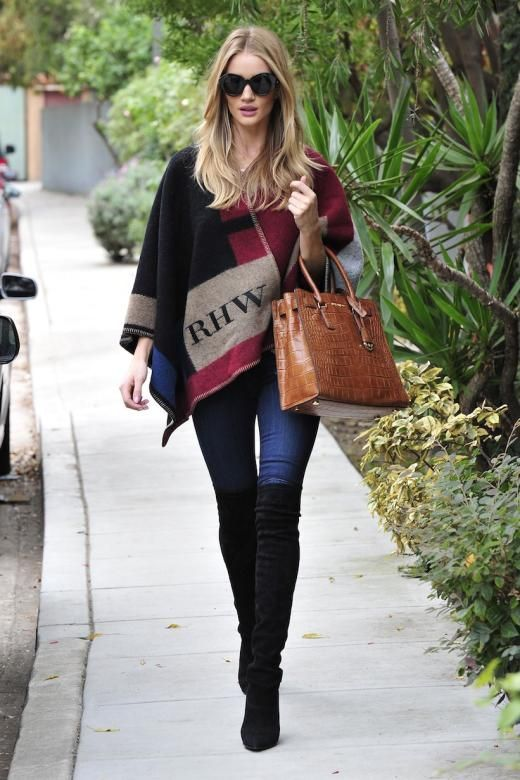 """Für alle, die von """"Übergangsjacke"""" nichts hören wollen, zeigt Rosie Huntington Whiteley, wie ein stilsicherer Herbstlook geht. Die Overknee-Stiefel machen die Jeans-Poncho-Kombination sogar ein bisschen sexy."""