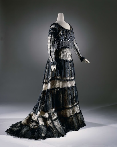 c. 1900 Skirt with train belonging to a gown of black lace on cream satin underskirt, with wide flounces of Chantilly lace and machine made lace. Designer Lucien Andrain