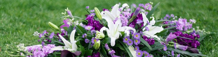 "Diamond-shaped low casket spray featuring white stargazer lilies, light and dark purple stock, light and dark purple gladiolas, light purple September flowers, egg plant calla lilies, white tiger lilies, purple delphinium, tropical leaves, and ""Lemon Leaf"" salal."