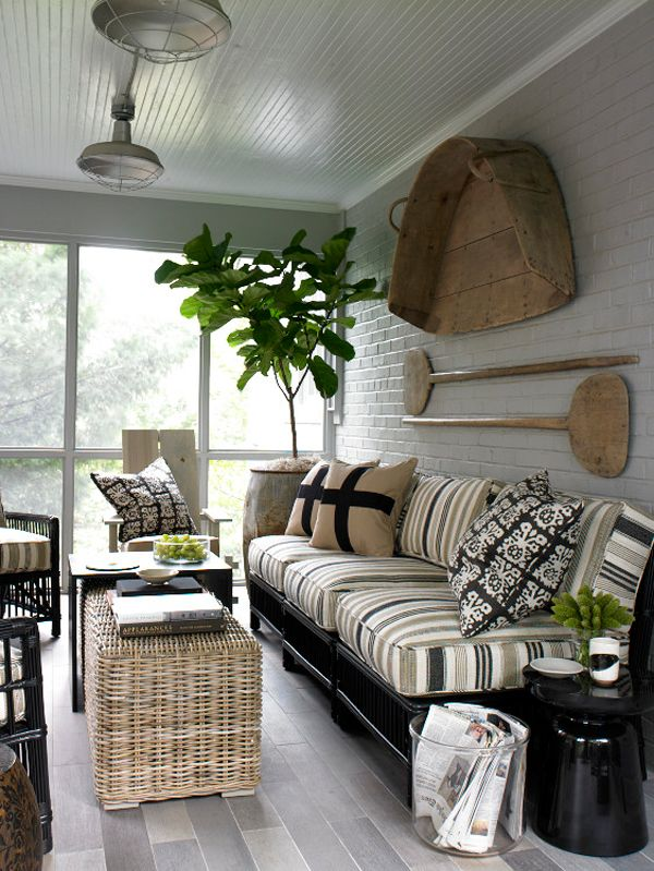 Dark base to the sofa, simple stripes, wicker, Natural wood on the walls with worn, old wood tied together with a tropical plant.
