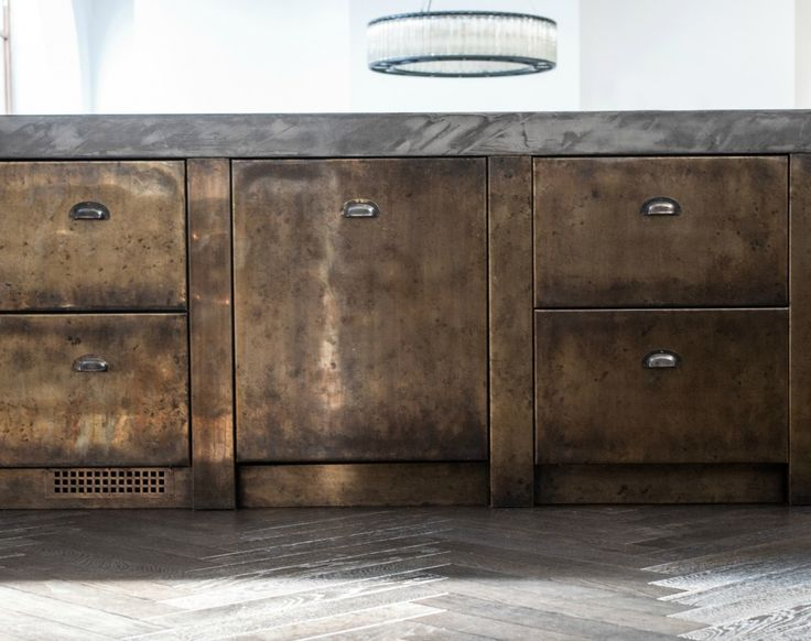 Burnt and ebonised oak units below the polished concrete countertop provide a sleek industrial look
