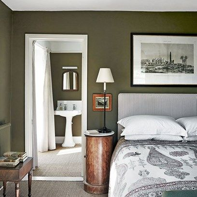 The Main Bedroom in Georgian Country House. The main bedroom with a view to the bathroom. Both have been painted a rich olive green.