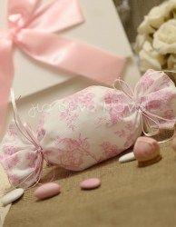 Μπομπονιέρα βάπτισης καραμέλα σε λευκό ύφασμα με ροζ ρομαντικά λουλούδια στολισμένη με λευκά ροζ κορδελάκια σατέν.<br> <br> Στην περίπτωση που διαλέξετε την συσκευασία ολοκληρωμένη μπομπονιέρα, η τιμή συμπεριλαμβάνει 5 κουφέτα αμυγδάλου Α΄ποιότητας Χατζηγιαννάκη Super No 2. Αν επιθυμείτε άλλη ποιότητα κουφέτων, παρακαλούμε επιλέξτε όπως θα δείτε παρακάτω.<br> Εάν επιλέξετε άδετη μπομπονιέρα, τα υλικά έρχονται στο χώρο σας μετρημένα και κομμένα μαζί με ένα δείγμα ολοκληρωμέ...