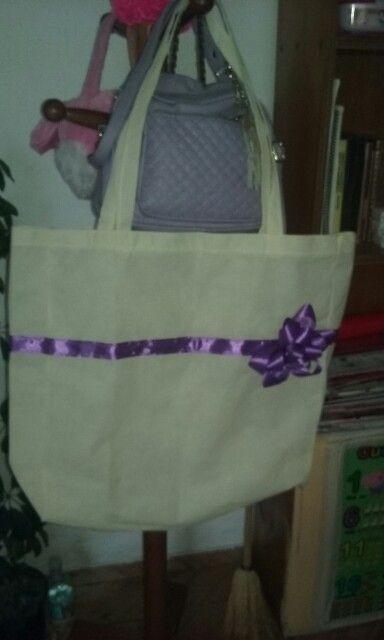bolsa para las compras. tela tnt color crudo. con cintas moradas.