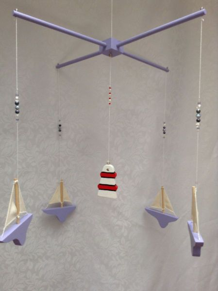 Sailing boat mobileThis mobile consists of 4 sailing boats drifting around a central lighthouse.Other colours available on request.Please email