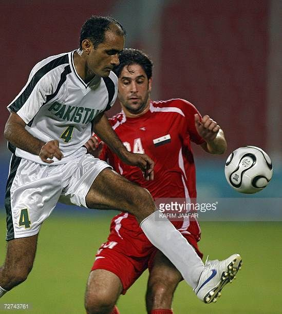 Syrian national team football player Rafe Raja vies with Tanveer Ahmed of Pakistan during their Men's Round 2 Group F Match at the 15th Asian Games...